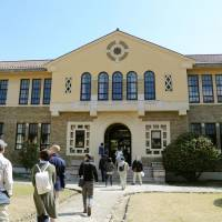 Architecture fans take part in a campus tour at Kobe College, which houses historic buildings designed by William Merrell Vories, on March 26.   KYODO