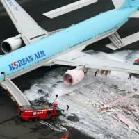 White smoke streams from the port engine of a Korean Air Boeing 777 Friday on runway C of Haneda airport. | KYODO