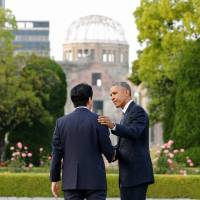 U.S. President Barack Obama and Prime Minister Shinzo Abe, after laying wreaths in front of a cenotaph as the atomic bomb dome is seen in the background at Hiroshima Peace Memorial Park on Friday.    POOL PHOTO VIA REUTERS