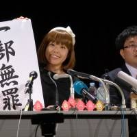 Megumi Igarashi, 44, addresses reporters on Monday with a banner that says 'partially innocent.' | SHUSUKE MURAI