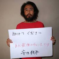 An image believed to be that of Japanese freelance journalist Jumpei Yasuda, who went missing in Syria in 2015, shows him holding a sign bearing the message 'Please help. This is the last chance.' The image was allegedly sent to media by Yasuda's captors via a mediator. | THE JAPAN TIMES