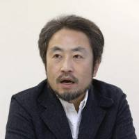 Jumpei Yasuda speaks during an interview in Japan in February 2015. A suspected hostage photo emerged Monday that shows Yasuda wearing an orange outfit and holding a sign saying 'Please help. This is the last chance.' | KYODO