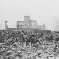 Atomic age dawns: An Allied correspondent stands amid rubble in Hiroshima on Sept. 8, 1945, a month after the first atomic bomb ever used in warfare was dropped by the U.S. on the city. By the end of the year, the bombs dropped on Hiroshima and Nagasaki and their fallout had killed over 210,000 people, mostly civilians. | STANLEY TROUTMAN / AP