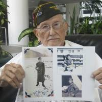 Arthur Ishimoto, 93, a U.S. Army veteran, poses with archival photographs of himself as he is interviewed in Honolulu. Like many Americans, Ishimoto believes dropping the atomic bombs on Nagasaki and Hiroshima saved the lives of possibly a million Americans and even more Japanese. | AP