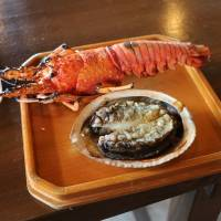 Freshly grilled Japanese spiny lobster and abalone at the Hachiman-kamado ama divers' hut in Toba, Mie Prefecture. | KYODO