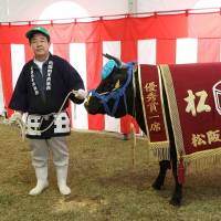A farmer stands alongside a cow named Momomiya, which attracted the highest bid at an auction in 2015. | J.J. O'DONOGHUE