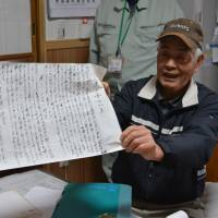 Cattle farmer Jiro Tochigi holds an autobiography penned by the grandmother of the current president of Wadakin, a restaurant in Mie Prefecture that specializes in serving Matsusaka beef. | J.J. O'DONOGHUE