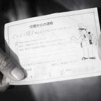 Tanaka shows a certificate handed out by local police to show they have called upon her once a week to check on her well-being | ROB GILHOOLY