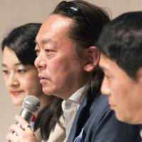 Tetsuya Ando, one of the founders of White Ribbon Campaign Japan, speaks during an event in Tokyo to launch the organization on May 1. To Ando's right is Hiromi Nakano, president of anti-sexual abuse NGO Shiawase-namida and, to his left, Inagi City lawmaker Akira Sasaki, who as a child was physically abused at the foster home at which he was raised.  | ROB GILHOOLY