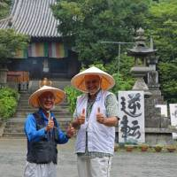 Albert Kirch (right) from Basel, Switzerland, and Mikio Nakaoka from Osaka pose for a photo during their visit to Ishite-ji, a Buddhist temple in Matsuyama, Ehime Prefecture. | KYODO