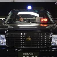 No free ride: A driver checks a Nihon Kotsu taxi at the firm's garage in Tokyo.   BLOOMBERG