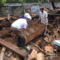 Rescuing memories: Shaun O'Dwyer (left) and other volunteers extract a chest containing photo albums and other valuables from the ruins of a house in Mashiki, Kumamoto Prefecture, days after the quakes last month. | IT'S NOT JUST MUD