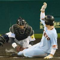 Hanshin catcher Fumihito Haraguchi tries to tag out Yomiuri's Seiji Kobayashi during the third inning of Wednesday's game against the Giants. Haraguchi made the tag but the umpires overturned the ruling and gave the Giants the run. | KYODO