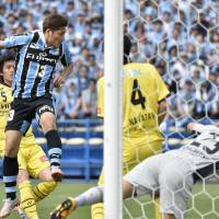 Yoshito Okubo (13) heads in a goal for Kawasaki Frontale during a 2-1 win over Kashiwa Reysol on Sunday. | KYODO