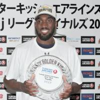 Ryukyu Golden Kings' Evan Ravenel holds his award for playoff MVP after Sunday's bj-league championship game win over the Toyama Grouses. | YOSHIAKI MIURA
