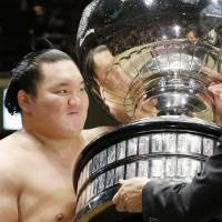 Yokozuna Hakuho receives the trophy from Prime Minister Shinzo Abe on Sunday after winning the Summer Grand Sumo Tournament. | KYODO