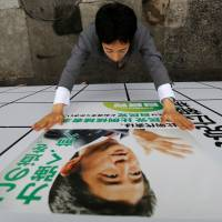An LDP staff member puts up a poster for the July 10 Upper House election featuring Prime Minister Shinzo Abe at the party's headquarters in Tokyo on Wednesday. The slogan on the poster reads: 'Moving forward with strength.' | REUTERS