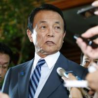 Finance Minister Taro Aso speaks to reporters following an emergency meeting between the government and the Bank of Japan at the Prime Minister's Office in Tokyo on Monday morning. | KYODO