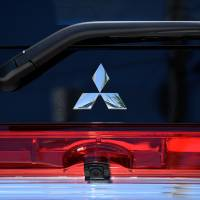 The Mitsubishi Motors Corp. logo is displayed on a car sitting on display at one of the company's dealerships in Kawasaki.   BLOOMBERG