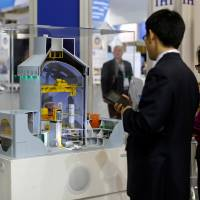 Visitors look at a nuclear power plant station model by American company Westinghouse at the World Nuclear Exhibition 2014, the trade fair event for the global nuclear energy sector, in Le Bourget, near Paris.   REUTERS
