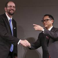 Gill Pratt, chief executive officer of Toyota Research Institute, and Toyota Motor Corp. President Akio Toyoda shake hands during a news conference on artificial intelligence in Tokyo last November. | AP