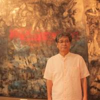 A portrait of history: Michio Sakima, director of Sakima Art Museum, stands in front of panels of paintings by the late couple, Iri and Toshi Maruki, that depict the 1945 Battle of Okinawa. | KYODO