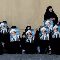 Bahraini anti-government protesters hold posters of top Shiite cleric Sheik Isa Qassim as they wait for a demonstration in Karrana, Bahrain, in May 2013. | AP