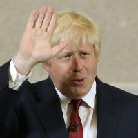 Former London mayor Boris Johnson waves after he announced that he will not run for leadership of Britain's ruling Conservative Party in London on Thursday. | AP