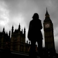 A woman walks past the Houses of Parliament and the Big Ben clock tower, on the day of the EU referendum, in central London, Thursday. | REUTERS
