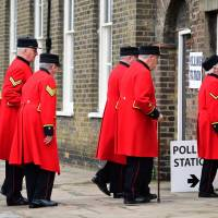 Chelsea pensioners are ushered into a polling station to cast their ballot papers at the Royal Hospital in Chelsea, west London, Thursday, as Britain holds a referendum to vote on whether to remain in, or to leave the European Union (EU). | AFP-JIJI
