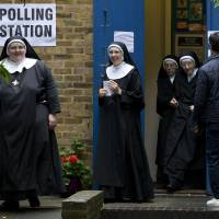 Nuns leave after casting their votes at a polling station in London Thursday as Britain holds a referendum on whether to stay or leave the European Union (EU). | AFP-JIJI