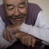 Meng Xianren, 85, one of the few remaining mother-tongue speakers of the Manchu language, relaxes at the home of a friend in the Chinese village of Sanjiazi last month. | AFP-JIJI