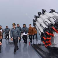 Indonesian President Joko Widodo walks on the deck of the Indonesian Navy ship KRI Imam Bonjol together with members of his Cabinet as the ship sails off the Natuna Islands in Riau Islands province on June 23. | REUTERS