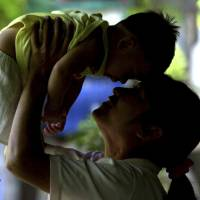 An HIV-positive mother plays with her son, who did not contract the virus from her, in Phetchaburi province, south of Bangkok, in this file photo from June 17, 2004. | AP