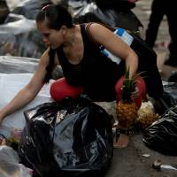 A pregnant woman who did not want to be named holds a pineapple in one hand as she continues to pick through garbage bags outside a supermarket in downtown Caracas June 2. Unemployed people converge every dusk at the trash heap to pick through rotten fruit and vegetables tossed out by nearby shops. | AP