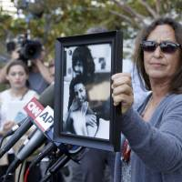 Janet Wolfe holds a photo of her brother, Randy Wolfe, better known as Randy California, a member of the band Sprit, outside federal court,Thursday in Los Angeles. A jury found Thursday that the band Led Zeppelin did not lift a passage from the Spirit song 'Taurus' for the intro to their rock classic 'Stairway To Heaven.' | AP