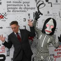 Swiss Ambassador to Japan Urs Bucher (left) poses for photos with 'Dada,' a monster in a popular TV series created as an extension of Dadaism, in Tokyo on May 19. | KYODO