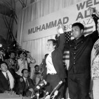 Muhammad Ali makes a show of strength at a press conference at the Keio Plaza Hotel, prior to what was billed the bout of the century.    KYODO