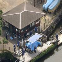 Investigators search the pond where body parts were found in Himonya Park, Tokyo's Meguro Ward, on Thursday. | KYODO
