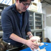 Kazuhiro Sakaue, senior researcher of anthropology at National Museum of Nature and Science, observes a restored skull believed to be that of Italian missionary Giovanni Battista Sidotti, at a laboratory in Tsukuba, Ibaraki Prefecture, in April. | AFP-JIJI