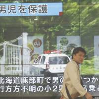 An electronic board in Tokyo on Friday shows a local news report that a missing boy was found in Hokkaido. Headline, top on the screen, reads: 'Boy is in custody.' | AP