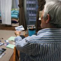 An elderly man living on welfare displays photos from his youth at his home in Tokyo's Shinjuku Ward in May. | KYODO