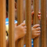 Children are seen through a baby safety gate as they play at Futaba Baby Home in Tokyo on June 21. | REUTERS