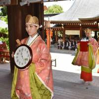 Women clad in ancient Japanese court dress walk holding clocks during an annual clock festival on Friday at Omi Shrine in Otsu, Shiga Prefecture. Emperor Tenji (626-672), said to be the founding father of the clock time system in Japan, is enshrined there as its deity. | KYODO