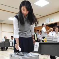Chiho Tatsumi, 18, casts an early ballot Thursday in Mino, Osaka Prefecture, becoming the first 18-year-old in Japan to vote. | MAINICHI SHIMBUN / KYODO
