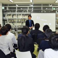 An employee talks to his colleagues as part of a workplace-enhancement program at contract systems developer ISA Plan Inc. in Tokyo on April 22. | KYODO