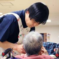 A nursing care worker helps a senior eat at a nursing care facility in Tokyo in March. Japan's care-worker shortage is becoming increasingly serious. | KYODO