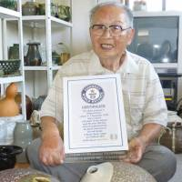 Shigemi Hirata, a 96-year-old man from western Japan, poses for a photo at his home on Friday with a Guinness World Records certificate recognizing him as the world's oldest graduate. | KYODO