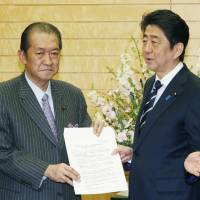 Liberal Democratic Party lawmaker Kunio Hatoyama (left) meets Prime Minister Shinzo Abe in February regarding the relocation of government institutions. | KYODO
