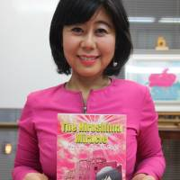 Taeko Tada holds a copy of the manga she wrote about women who survived the atomic bombing, seen on May 25. | KYODO